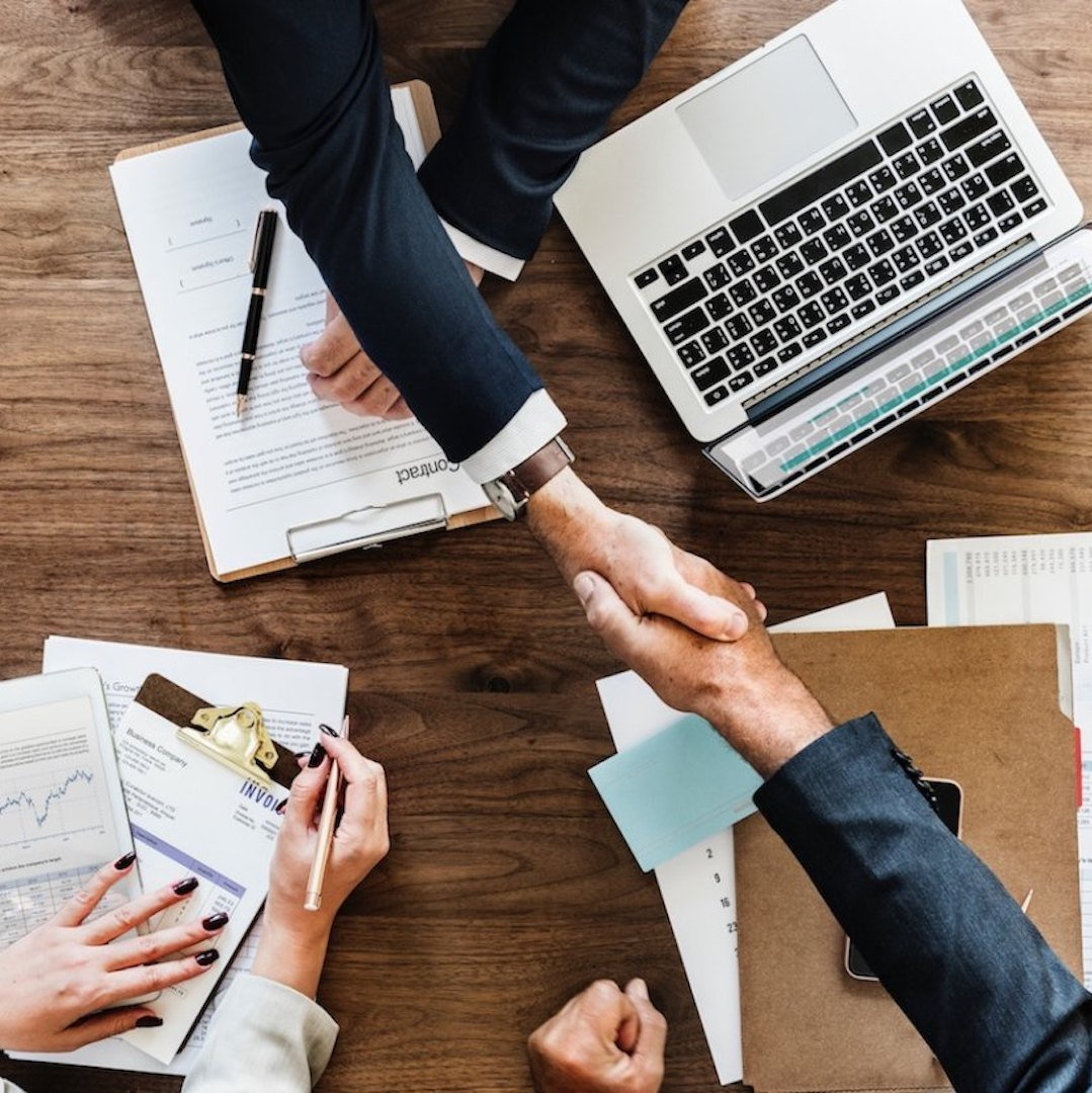handshake between two business partners over a wooden table with a laptop and documents