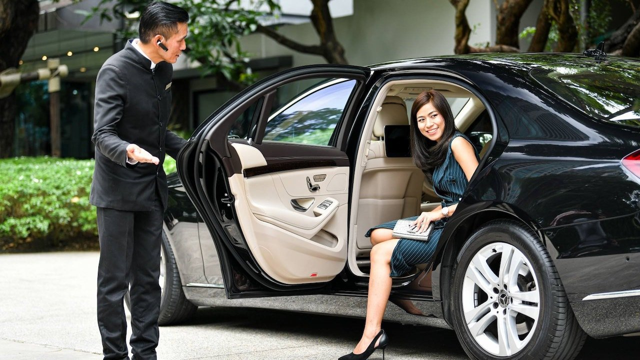 private chauffeur opening the door to a young girl getting out from a luxury limousine in Thailand