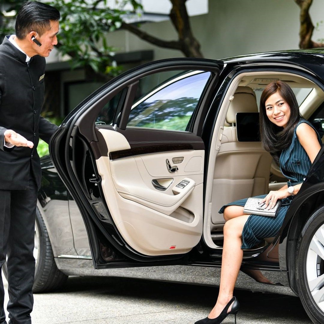 asian woman getting out of a private limousine with the chauffeur opening the door for her