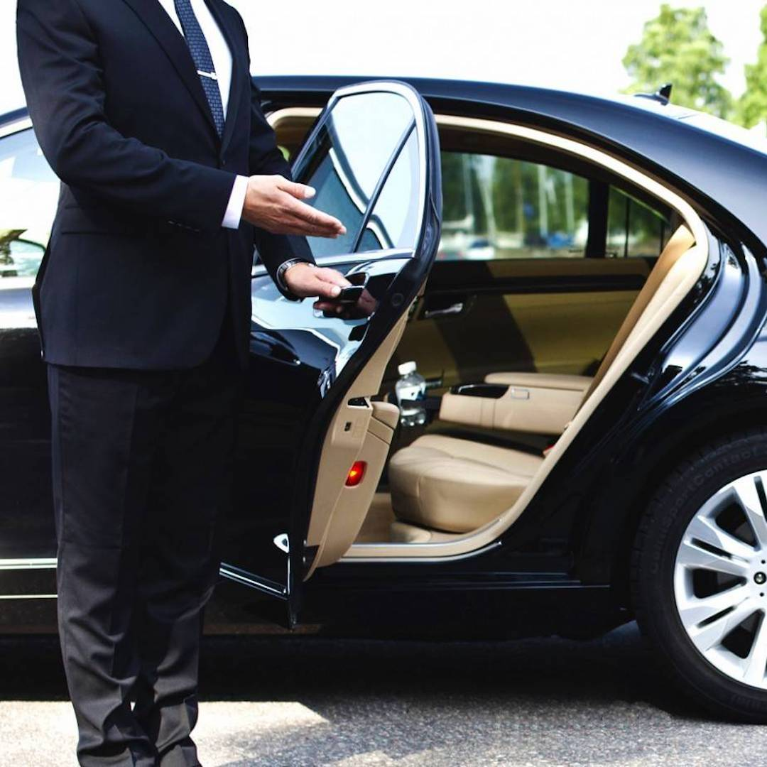 chauffeur opening the door of a luxury limousine in Thailand