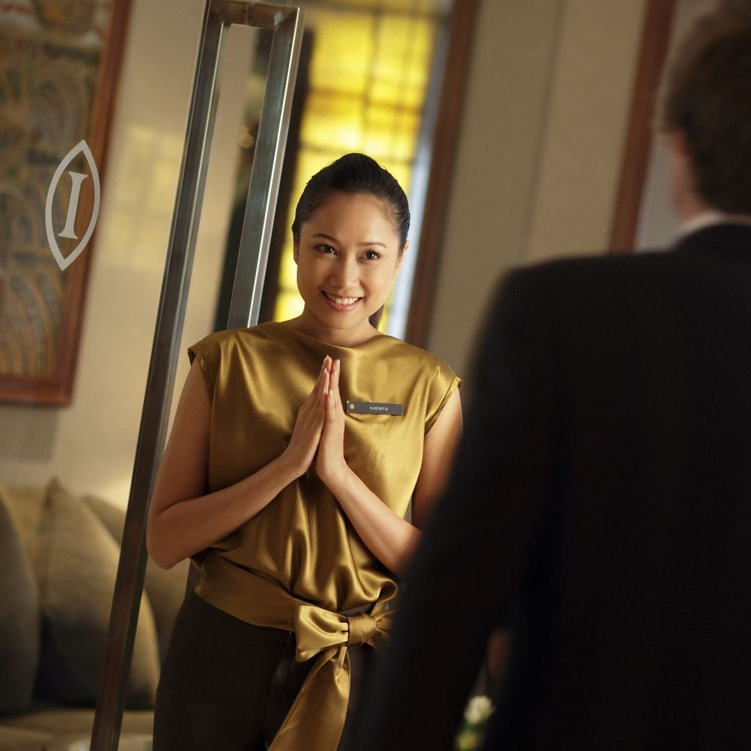 Thai hostess welcoming a wealthy client to a concierge service in Thailand