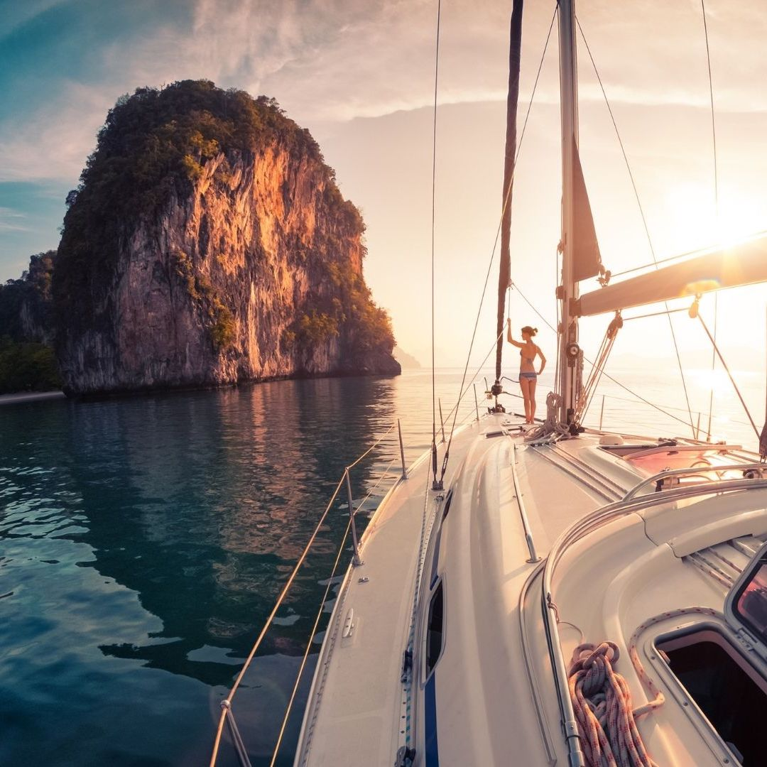 woman on a sailing boat during sunset in Thailand